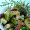 Warm Brussels Sprout Salad with Hazelnuts and Cranberries Recipe - Roasted Brussels sprouts are tossed with a maple-bacon dressing, toasted hazelnuts, and dried cranberries for a unique and delicious salad.