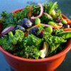 Super Summer Kale Salad Recipe - This kale salad recipe delivers a big bowl of vegetables, fruits, nuts, and seeds for a filling potluck favorite.
