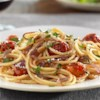Gluten Free Spaghetti with Caramelized Red Onions, Cherry Tomatoes, Pine Nuts, and Pecorino Cheese Recipe - Roasted tomatoes and caramelized onions bring sweet-savory flavors to spaghetti tossed with grated cheese and toasted pine nuts.