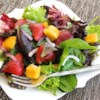 Strawberry-Mango Mesclun Salad Recipe - Mango, strawberries, and sweetened dried cranberries are a vibrant addition to mixed greens tossed with an oil and balsamic vinegar dressing.