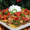 Over the Top Nachos Recipe - Ground beef is the key to these hearty classic nachos--it's generously spread over the chips before cheese and toppings.