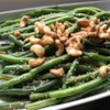 Japanese-Style Sesame Green Beans Recipe - Fresh green beans are cooked whole in canola and sesame oils, then splashed with soy sauce and served with toasted sesame seeds.