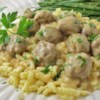 Swedish Meatballs (Svenska Kottbullar) Recipe and Video - Swedish meatballs made with ground beef and pork are gently spiced, baked, and served with brown sour cream gravy in this old family favorite.