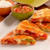Smoked Andouille Quesadilla Recipe - Quesadilla wedges with slices of browned andouille sausage, provolone cheese, roasted peppers, veggies, and more make delicious appetizers or hors d'oeuvre for any festive event.