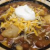 Southwest Stew Recipe - Browned ground beef is combined with canned pinto beans, tomatoes and whole corn kernels in this soup seasoned with picante sauce and cumin.  Serve topped with grated cheddar cheese.