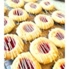 White Chocolate Raspberry Thumbprint Cookies Recipe - Raspberry thumbprint cookies get a drizzle of white chocolate and a sprinkling of red sugar for a festive Christmas cookie perfect for gifts or parties.