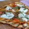 Pizza On The Grill I Recipe and Video - With this recipe, you'll make the garlic and basil pizza dough from scratch, and learn the tricks of grilling a perfect pizza that features tomatoes, olives, roasted red pepper, and basil. Makes two medium pizzas.