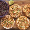 Chicken Tinga Tostados Recipe - This authentic Mexican recipe I picked up while living in Mexico.  It has a spicy, smoky flavor from chipotle peppers.  It is perfect for a buffet where people can serve themselves and even better heated up as leftovers the next day! If this is too spicy for you, try using less chipotle peppers.