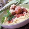 Chicken Meatballs and Spaghetti Recipe and Video - Chicken meatballs are simmered in a homemade tomato sauce and served with spaghetti noodles.