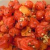 Roasted Tomatoes with Garlic Recipe - Grape tomatoes are tossed with sliced garlic and roasted until they pop in this simple, yet impressive side dish.
