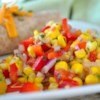 Southwestern Roasted Corn Salad Recipe - This mouthwatering grilled corn salad is so great, it may just outshine your entree! Peppers, onion, and corn are tossed together and served with a lime and cilantro dressing.