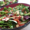 Baby Greens with a Warm Gorgonzola Dressing Recipe - This baby green salad is tossed with a warm Gorgonzola dressing, bacon, and toasted almonds.