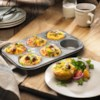 Amazing Muffin Cups Recipe - Eggs, sausage, red bell pepper, and cheese are baked in hash brown potato 'cups' for a delicious breakfast that will feed a crowd.