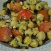 Chickpea Salad with Red Onion and Tomato Recipe -  Chilling makes all the difference in this great salad. And the generous splash of olive oil and lemon juice brings out all the great veggie flavors. The chick peas add variety and a nice texture.