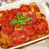 Scalloped Tomatoes Recipe - Basil, brown sugar, bread cubes and onions are cooked up with thick, juicy slices of tomato, and then baked in the oven until your kitchen smells wonderful.