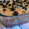 Taco Dip Recipe - We love refried beans and this dip has lots. Said beans are spread into a pan, then slathered with spicy sour cream and salsa. Tomatoes, lettuce, onions and olives come next, with a sprinkling of Cheddar cheese on the top. Serve with chips and dip in.