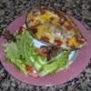 Stuffed Eggplant Parmesan Recipe - Eggplant centers are cooked with onion, garlic, and seasonings, then re-stuffed into the eggplant, coated with tomato sauce, cheese, and bread crumbs, and baked until tender and bubbly.