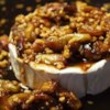 Figs and Toasted Almonds Brie Recipe - Brie cheese smothered with fresh figs cooked with brown sugar, vanilla, and almonds, then baked until almost melted. Serve warm with water crackers as a wonderful holiday appetizer or special treat during fig season. Canned figs in syrup may be substituted for fresh by reducing the brown sugar to 1/4 cup and replacing the water with syrup.