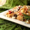 Mediterranean Pasta Recipe - Chicken breast chunks flavored with bacon, artichoke hearts and herbs in a tomato sauce all over a steaming bowl of linguine.