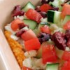 Greek Layer Dip Recipe - This 5-layer dip is full of bright and briny flavors. Serve it with pita chips or crackers for a deliciously Greek-inspired snack.