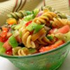Three Pepper Pasta Salad Recipe - Orange, yellow, and red peppers are tossed with an olive oil and vinegar dressing and tricolor pasta.