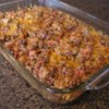 Taco Bake II Recipe - The whole family will enjoy this taco casserole consisting of ground beef, tomatoes and sour cream, then seasoned with taco seasoning. It's all layered with corn tortilla chips and Colby and Monterey Jack cheeses, then baked until the cheeses are melted and bubbly.