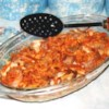 Creamy Potato Pork Chop Bake Recipe - Sauteed pork chops are baked over a comfy nest of hashbrown potatoes and Cheddar cheese in a sour cream sauce, with some crunchy onion rings thrown in to keep things interesting. Add some green beans and you have a warm and homey one-dish meal.