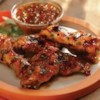 Grilled Chicken Wings with Sweet Red Chili and Peach Glaze Recipe - These succulent chicken wings are grilled with a glaze of peach-apricot preserves, Thai sweet red chili sauce, fresh cilantro and lime juice.