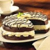Chocolate Banana Cream Cake Recipe - Devil's food cake is layered with bananas and a creamy pudding mixture then drizzled with chocolate for a rich and elegant dessert.