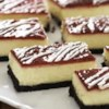White Chocolate-Raspberry Cheesecake Bars Recipe - Classic cheesecake bars become a touch more elegant with a white chocolate filling.  A layer of raspberry preserves and drizzle of white chocolate take them over the top.