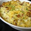 Cheesy Scalloped Potatoes with Ham Recipe - This hearty dish of scalloped potatoes and ham has just a bit of Cheddar cheese and green peas in a creamy white sauce.