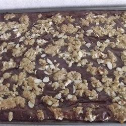 Fudge Nut Oatmeal Bars Recipe - Sliced almonds and almond extract give these chocolatey oatmeal bars an extra nutty flavor.