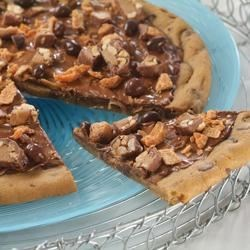 Candy Shop Pizza Recipe - Kids and adults will delight as they bite into this Candy Shop Pizza. The chewy chocolate chip cookie base is topped with creamy chocolate morsels, chunky peanut butter, and an assortment of chopped candy. This delicious treat also provides the perfect way to use up those trick-or-treating leftovers!