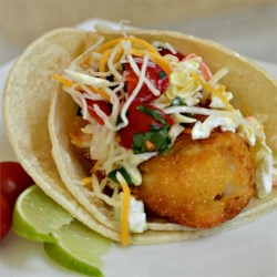Baja Style Fish Tacos Recipe - Beer batter-fried cod are topped with a creamy coleslaw, salsa fresca, and Mexican cheese for a fresh Baja-style fish taco.