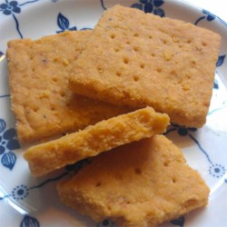 Cheddar Cheese Nippers Recipe - These cheesy little homemade crackers have a warm hint of cayenne in every bite. Make them square with a knife or roller, cut them into rounds, or even make cute shapes with cookie cutters.
