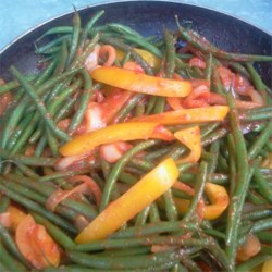Green Bean Stew Recipe - Green beans are layered in a pan with onions and green peppers and then sprinkled with turmeric. Tomato paste is spooned on and the pot is covered and cooked on the stove until everything is tender.