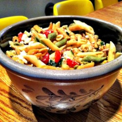 Sandy's Greek Pasta Salad Recipe - A pasta salad with Greek-inspired flavors is bright and colorful, thanks to colored rotini pasta, black olives, red tomatoes, and green cucumber. A fresh vinaigrette dressing and feta cheese add their finishing touches.