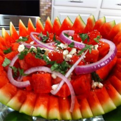 Herb Watermelon Feta Salad Recipe - Cubes of watermelon are tossed with handfuls of minced herbs, sliced onion, and feta cheese crumbles in this summer salad.