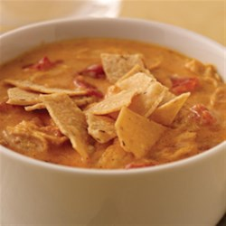 Cheesy Tortilla Soup Recipe and Video - A hearty, cheesy soup with diced tomatoes, shredded chicken, taco seasoning and lots of cheese, this soup will feed a hungry crowd and it's ready in 35 minutes.