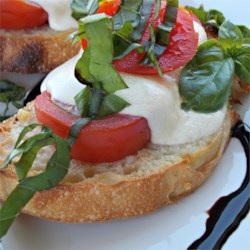 Baked Caprese Salad Recipe - Delightful toasted appetizer crostini made with fresh roma tomatoes and mozzarella cheese have all the flavor of a Caprese salad. The colorful little toasts are sprinkled with basil leaves and drizzled with olive oil.