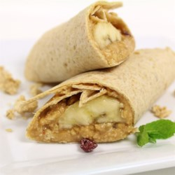 Emmi's Banana Wraps Recipe - These fun breakfast banana wraps are so easy a kid can help make them. Whole wheat tortillas are spread with peanut butter and filled with a banana half, coconut, and crunchy granola cereal.