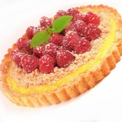 Raspberry Streusel Tart Recipe - A homemade custard is flavored with raspberry liqueur and baked in a tart shell, piled with raspberries, and studded with a fabulous sugar streusel.