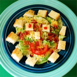 Smiley Salad Recipe -  What a fun way to get your child to eat a salad. First comes the lettuce, cheese and bacon bit in individual bowls. And then comes the decoration - croutons for the eyes and nose and a crescent of tomato for the mouth.