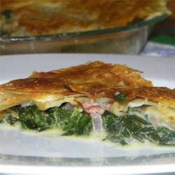 Spinach Pie with Pancetta Recipe - Topped with a golden sheet of puff pastry, this version of spanakopita includes crispy bits of pancetta mixed with feta cheese, spinach, garlic, and red onion.