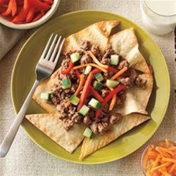 Spy Thai Beef Recipe - Ground beef seasoned with lime juice, ginger, and peanut butter is served atop crunchy baked wonton triangles with plenty of colorful vegetable topping options in this Thai-inspired dish.