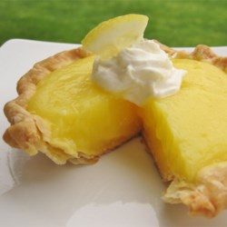 Lemon Butter Tarts Recipe - The filling for these diminutive treats is sweet and tart, with a delightful burst of grated lemon rind sweetness. The filling is spooned into 3-inch tart shells, covered with a dollop of meringue, and baked. This recipe yields a dozen.