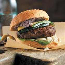 Olympian Burgers Recipe - Greek-inspired burgers are seasoned with olive tapenade and served with feta cheese, fresh spinach, and crisp-tender zucchini slices on whole-grain buns.