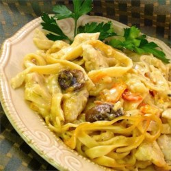Cheesy and Creamy Chicken Tetrazzini Recipe - Boneless chicken breast meat adds flavor to this lovely casserole of cooked fettuccine pasta in a creamy sauce brightened with cubes of red bell pepper. Three different cheeses top the dish.