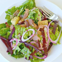 Beet and Balsamic Vinaigrette Salad Recipe - Crisp romaine hearts are tossed with julienned beets, sweet rings of red onion, Parmesan cheese and a balsamic vinaigrette and then sprinkled with hot, crumbled bacon.