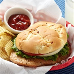 Pork Tenderloin Sandwiches with Chipotle Ketchup Recipe - Thin seasoned tenderloins are browned and served on toasted onion rolls with spicy ketchup, lettuce, and tomato and onion slices.